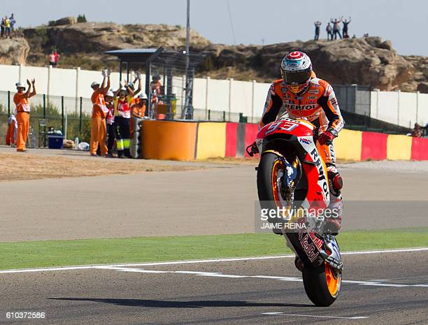 Repsol Honda's Spanish rider Marc Marquez does a wheelie to celebrate at the finish line after winning the Moto GP race of the Aragon Grand Prix at...