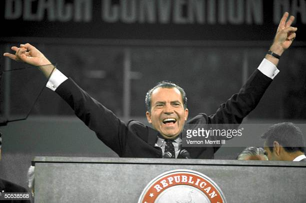 Repub Richard Nixon flashing vsign w fingers speaking into mike while standing at podium during Natl Convention