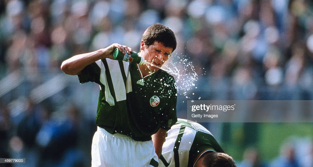 Republic of Ireland player Roy Keane cools himself down with water during a game circa 1993