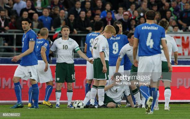 Republic of Ireland's John O'Shea holds his face after he was hit by Italy's Pazzini who was sent off during the World Cup Qualifying match at the...
