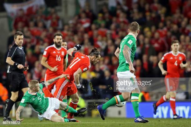 Republic of Ireland's midfielder James McClean slides in to make a tackle on Wales' midfielder Gareth Bale during the World Cup 2018 qualification...