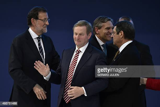 Republic of Ireland's Prime Minister Enda Kenny waves next to Spanish Prime Minister and leader of the rightwing PP Mariano Rajoy after a family...