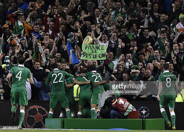 Republic of Ireland's striker Shane Long celebrates with teammates after scoring during a UEFA Euro 2016 Group D qualifying football match between...