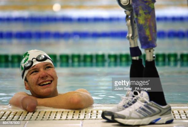 Republic of Ireland's Swimmer Darragh McDonald at the pool edge beside his prosthetic legs chatting to his coach Elizabeth Reid during a break in...