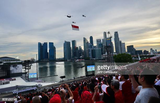 Republic of Singapore Air Force helicopters perform a flypast with a giant national flag during the 52nd Singapore National Day parade and...