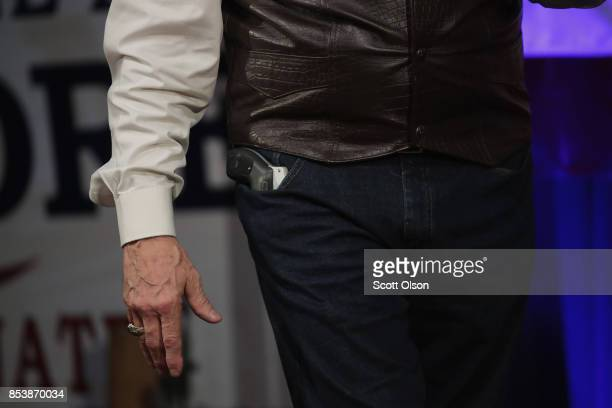 Republican candidate for the US Senate in Alabama Roy Moore displays a pistol to express his support for the Second Amendment as he speaks at a...
