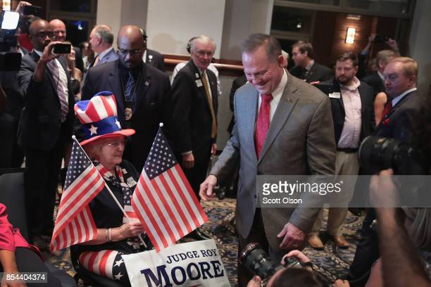Republican candidate for the US Senate in Alabama Roy Moore greets guests after arriving at an electionnight rally on September 26 2017 in Montgomery...