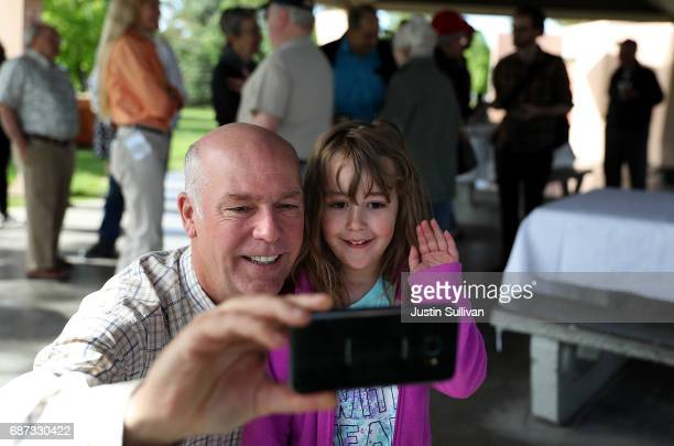 Republican congressional candidate Greg Gianforte takes a selfie with a young girl during a campaign meet and greet at Lions Park on May 23 2017 in...