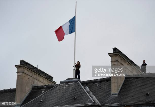 A Republican guard flies the French flag at half mast at the Elysee presidential Palace in Paris on May 24 2017 in tribute to the victims of the May...