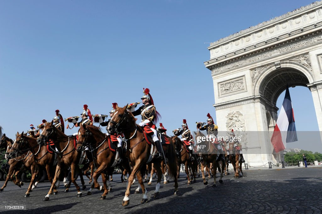 Republican Guard riders pass the Arch of Triumph on the Place de l'Etoile on July 14 2013 during the Bastille Day the French National Day parade in...