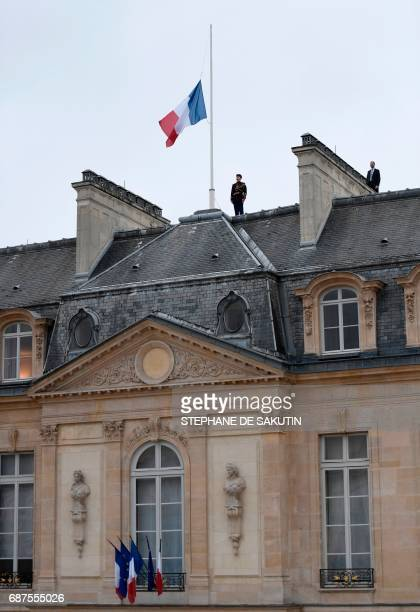 A Republican guard stands next to the French flag flying at half mast at the Elysee presidential Palace in Paris on May 24 2017 in tribute to the...