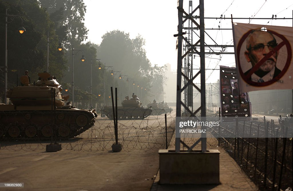 Republican Guard tanks sit a behind barbed wire fence near a banner saying 'No' to President Mohamed Morsi as they guard the Egyptian presidential palace in Cairo on December 14, 2012. Weeks of protests and violent clashes between rival camps that left eight people dead last week have failed to dissuade Morsi from holding the referendum, which will be staggered over a week. AFP PHOTO/PATRICK BAZ