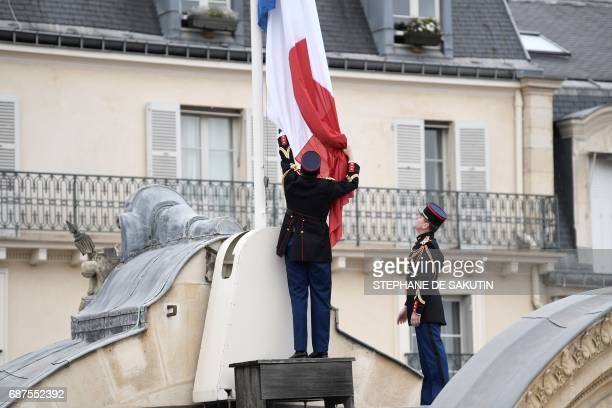 Republican guards fly the French flag at half mast at the Elysee presidential Palace in Paris on May 24 2017 in tribute to the victims of the May 22...
