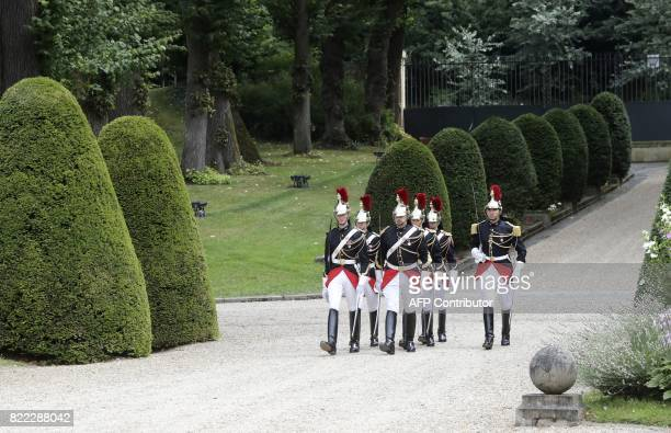 Republican guards part of an honour guard walk before talks aimed at easing tensions in Libya in La CelleSaintCloud near Paris on July 25 2017 The...