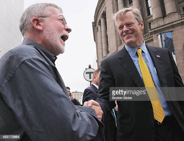 Republican gubernatorial candidate Charles Baker right greets a voter outside South Station in Boston on September 10 2014