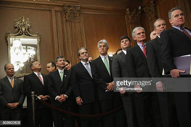 Republican members of the House of Representatives line up to watch Speaker of the House Paul Ryan sign legislation to repeal the Affordable Care Act...