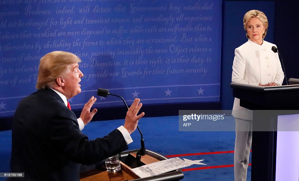 TOPSHOT - Republican nominee Donald Trump gestures as Democratic nominee Hillary Clinton looks on during the final presidential debate at the Thomas & Mack Center on the campus of the University of Las Vegas in Las Vegas, Nevada on October 19, 2016. / AFP / Mark RALSTON