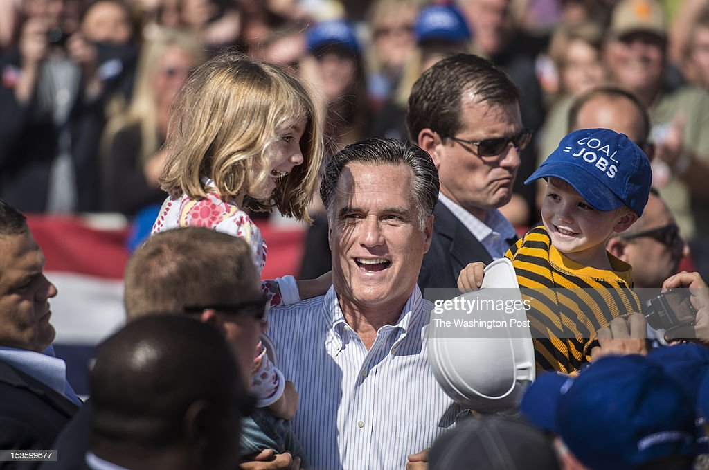 Republican nominee for President Governor Mitt Romney awkwardly picks up two kids during a rally in south western Virginia, in Abingdon, Virginia, on Friday, October, 5, 2012.