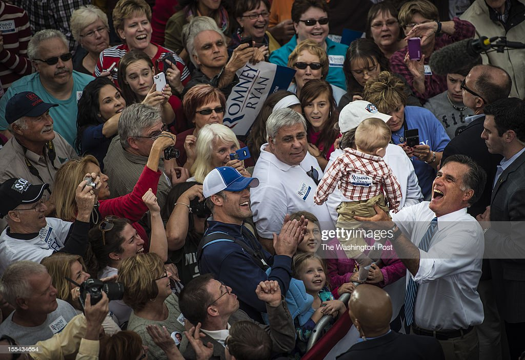 Republican nominee for President Governor Mitt Romney picks up a baby while shaking hands with supporters during a rally in historic downtown Lebanon...