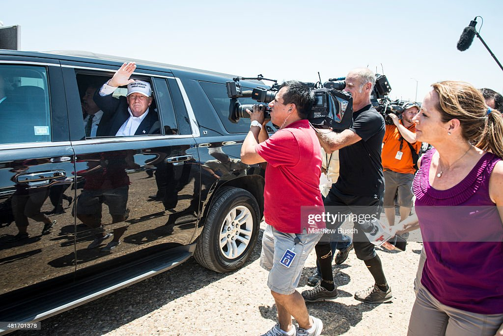 Republican Presidential candidate and business mogul Donald Trump talks to media from his car wearing a 'Make America Great Again' hat during his...