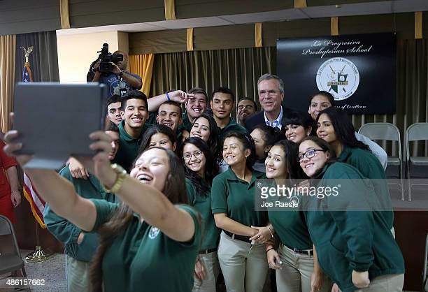 Republican presidential candidate and former Florida Gov Jeb Bush stands with students during a selfie photo shoot as he attends a town hall style...