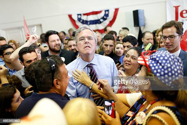 Republican presidential candidate and former Florida governor Jeb Bush allows a supporter to loosen his necktie during a rally on his 'Jeb Can Fix...