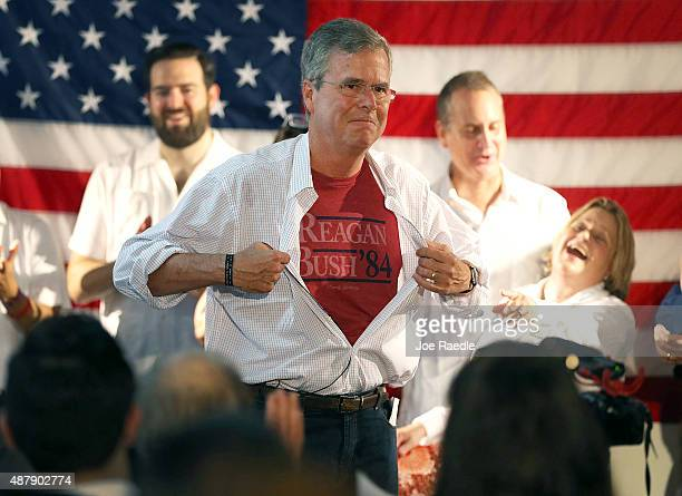 Republican presidential candidate and former Florida Governor Jeb Bush shows off a Reagan/Bush '84 teeshirt as he speaks during a Miami field office...