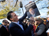 Republican presidential candidate and former Massachusetts Gov Mitt Romney holds up a poster of his father George Romney who was the former governor...
