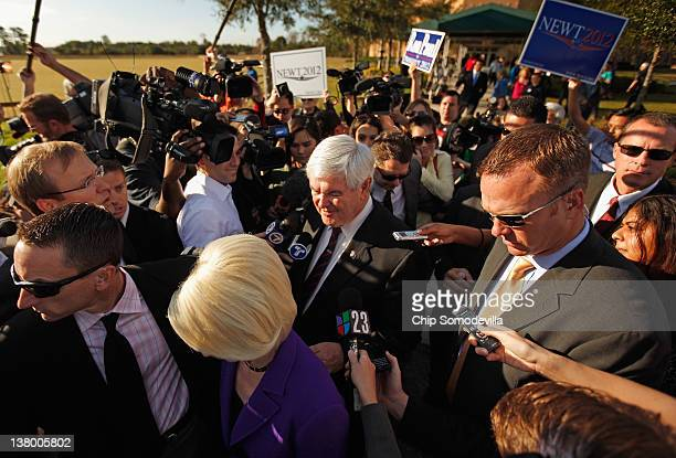 Republican presidential candidate and former Speaker of the House Newt Gingrich is surrounded by journalists and security guards as he campaigns with...