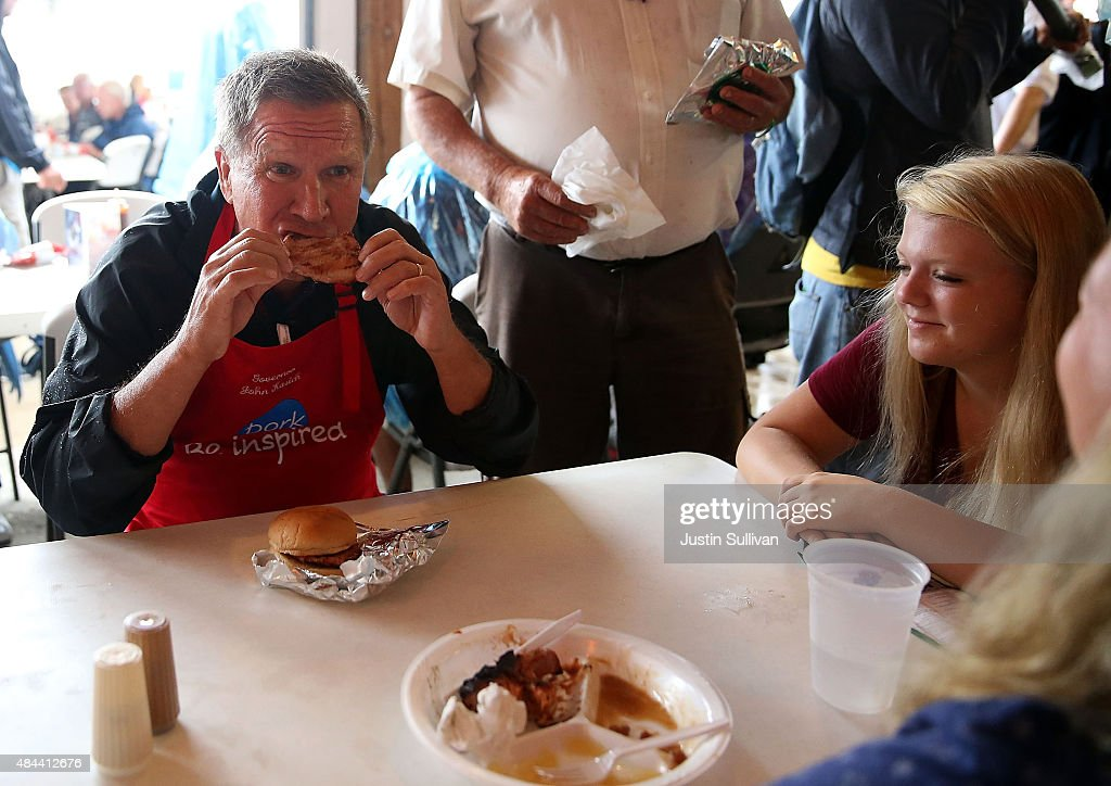Republican presidential candidate and Ohio Gov John Kasich eats a pork chop while visiting the Iowa Pork Producers Pork Tent during the Iowa State...