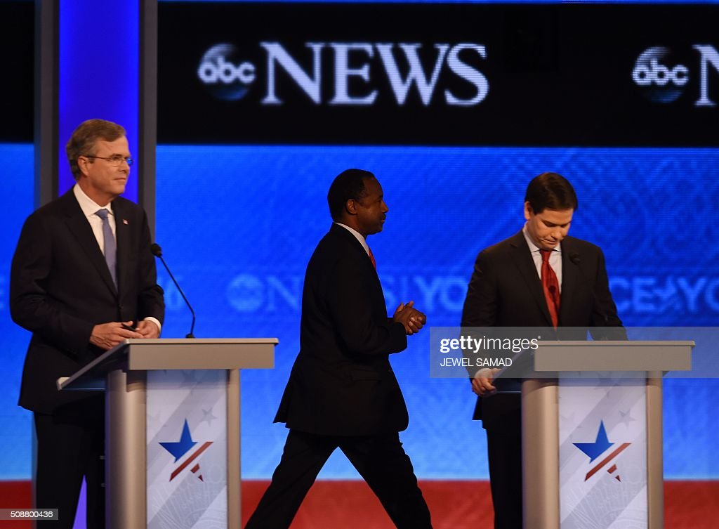 Republican presidential candidate Ben Carson(C) walks past fellow candidates Jeb Bush(L) and Marco Rubio (R) prior to the start of the Republican Presidential Candidates Debate on February 6, 2016 at St. Anselm's College Institute of Politics in Manchester, New Hampshire. Seven Republicans campaigning to be US president are in a fight for survival in their last debate Saturday before the New Hampshire primary, battling to win over a significant number of undecided voters. / AFP / Jewel Samad