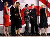 Republican presidential candidate Donald Trump and his son Donald Trump Jr embrace as Eric Trump Lara Yunaska Tiffany Trump and Vanessa Trump look on...