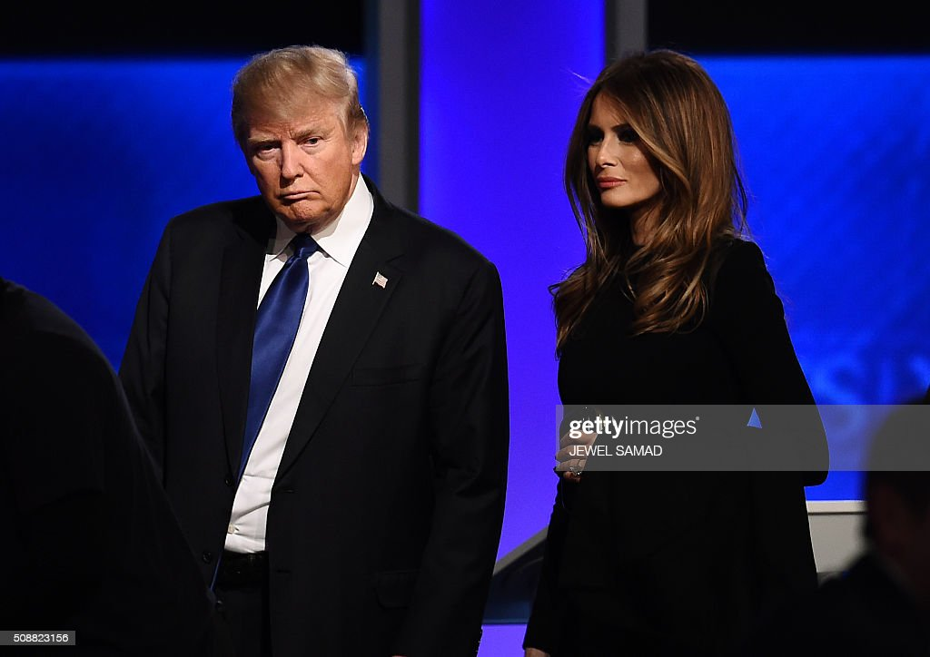 Republican presidential candidate Donald Trump and his wife Melania walk across the stage following the Republican Presidential Candidates Debate February 6, 2016 at St. Anselm's College Institute of Politics in Manchester, New Hampshire. Seven Republicans campaigning to be US president are in a fight for survival in their last debate Saturday before the New Hampshire primary, battling to win over a significant number of undecided voters. / AFP / Jewel Samad