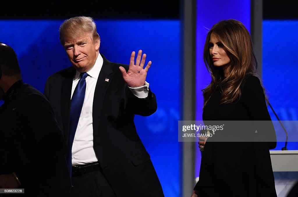 Republican presidential candidate Donald Trump and his wife Melania walk across the stage following the Republican Presidential Candidates Debate on February 6, 2016 at St. Anselm's College Institute of Politics in Manchester, New Hampshire. Seven Republicans campaigning to be US president are in a fight for survival in their last debate Saturday before the New Hampshire primary, battling to win over a significant number of undecided voters. / AFP / Jewel Samad