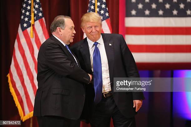 Republican presidential candidate Donald Trump and rival candidate Mike Huckabee shake hands during the rally for veterans at Drake University on...