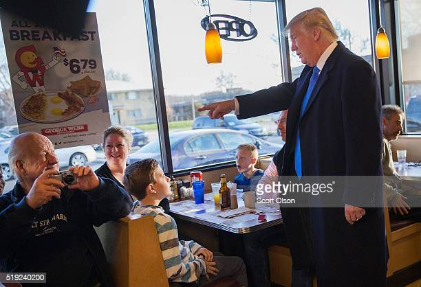 Republican presidential candidate Donald Trump chats with patrons and workers at a George Webb diner following an interview with Fox News on April 5...