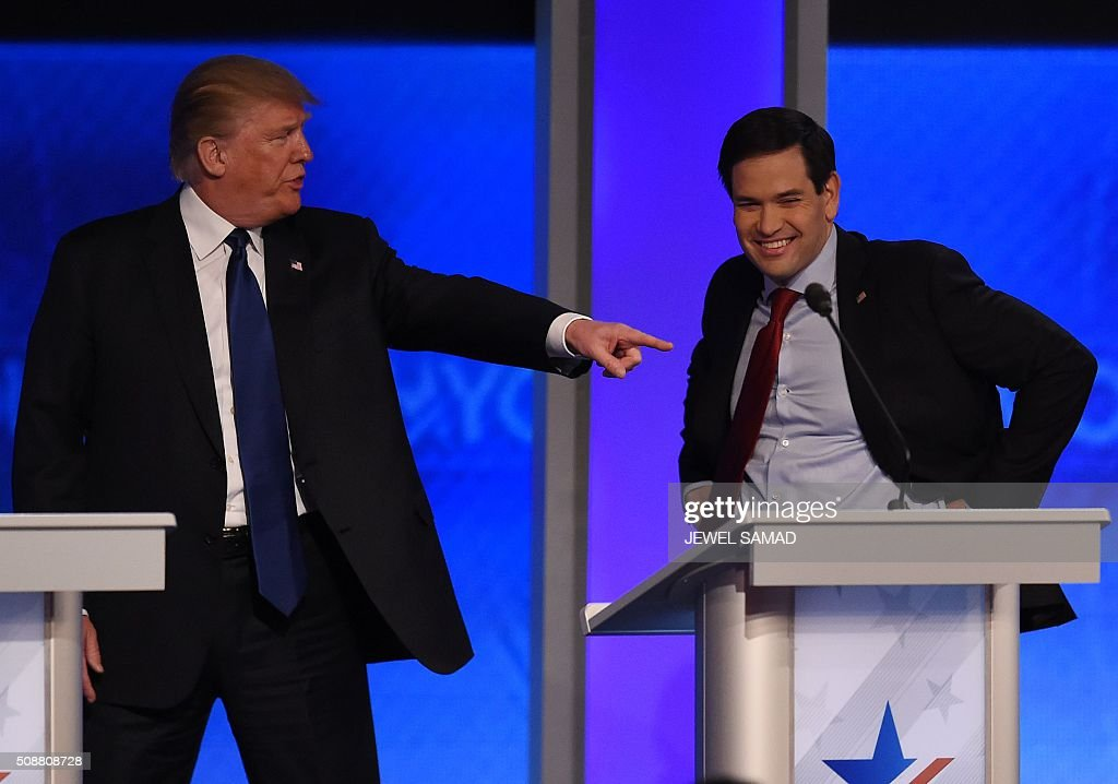 Republican presidential candidate Donald Trump (L) confers with fellow candidate Marco Rubio(R) during a break in the Republican Presidential Candidates Debate on February 6, 2016 at St. Anselm's College Institute of Politics in Manchester, New Hampshire. Seven Republicans campaigning to be US president are in a fight for survival in their last debate Saturday before the New Hampshire primary, battling to win over a significant number of undecided voters. / AFP / Jewel Samad