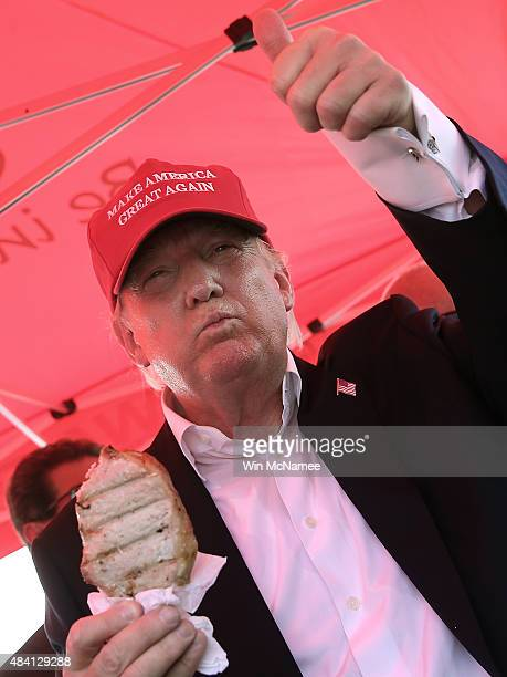 Republican presidential candidate Donald Trump eats a pork chop on a stick and gives a thumbs up sign to fairgoers at the Iowa State Fair on August...