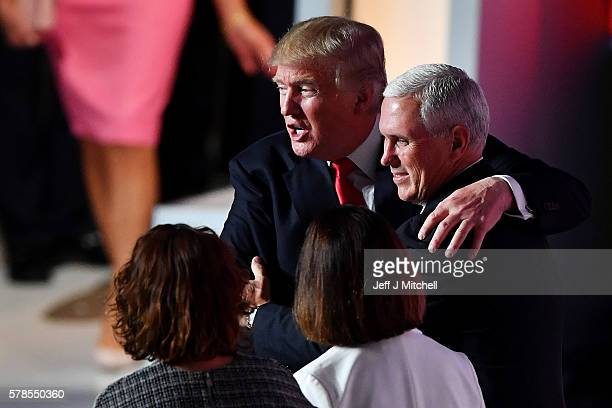 Republican presidential candidate Donald Trump embraces Republican vice presidential candidate Mike Pence after his speech on the fourth day of the...