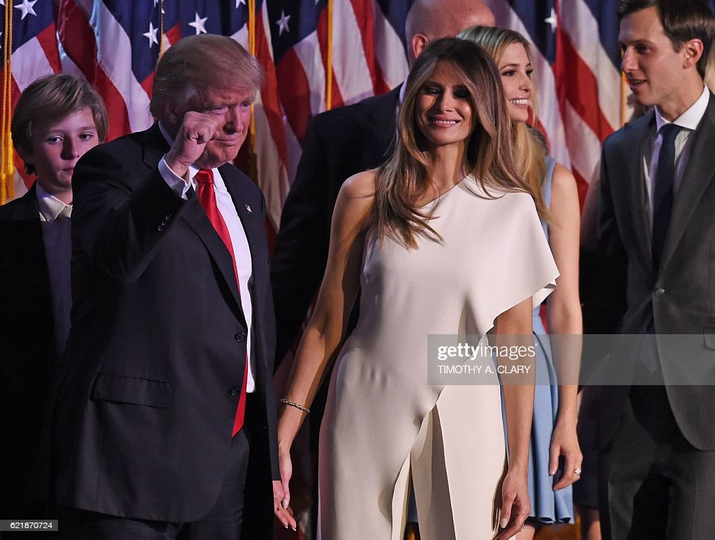 Republican presidential candidate Donald Trump, flanked by wife Melania, pumps his fist as he arrives with members of his family for an election night party at the New York Hilton Midtown in New York on November 9, 2016. Trump won the US presidency. / AFP / Timothy A. CLARY