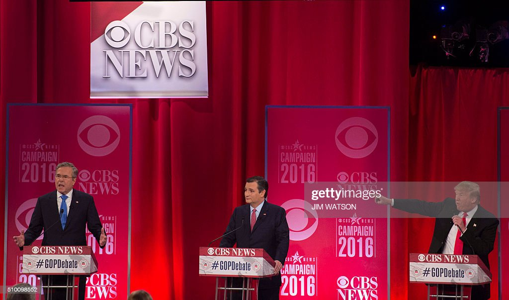 Republican presidential candidate Donald Trump (R) gestures towards fellow candidate Jeb Bush (L) as they argue through candidate Ted Cruz (C) during the CBS News Republican Presidential Debate in Greenville, South Carolina, February 13, 2016. / AFP / JIM WATSON