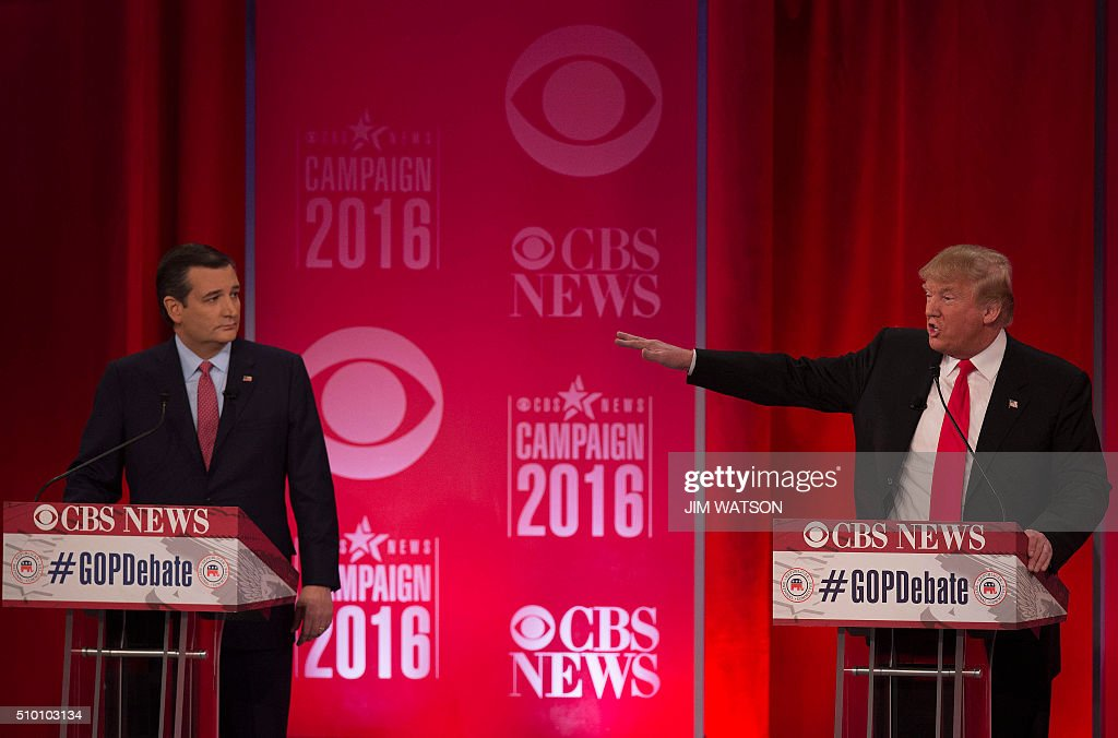 Republican presidential candidate Donald Trump (R) gestures towards Ted Cruz (L) during the CBS News Republican Presidential Debate in Greenville, South Carolina, February 13, 2016. / AFP / JIM WATSON
