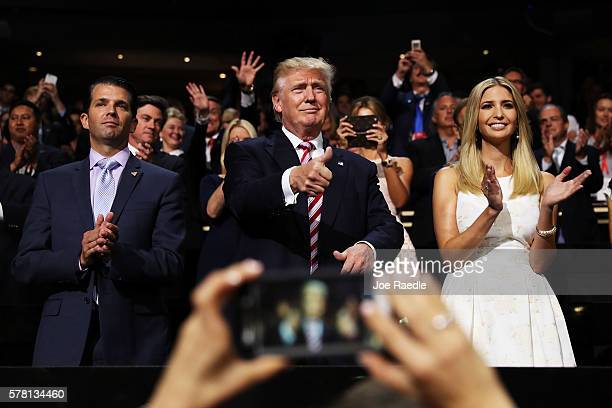 Republican presidential candidate Donald Trump gives a thumbs up as Donald Trump Jr and Ivanka Trump stand and cheer for Eric Trump as he delivers...