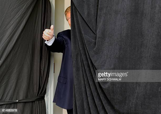TOPSHOT Republican presidential candidate Donald Trump gives a thumbs up from behind the curtain before taking the stage at an event on October 15...