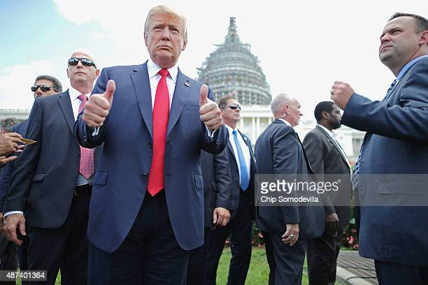 Republican presidential candidate Donald Trump gives a thumbs up to photographers during a rally against the Iran nuclear deal on the West Lawn of...