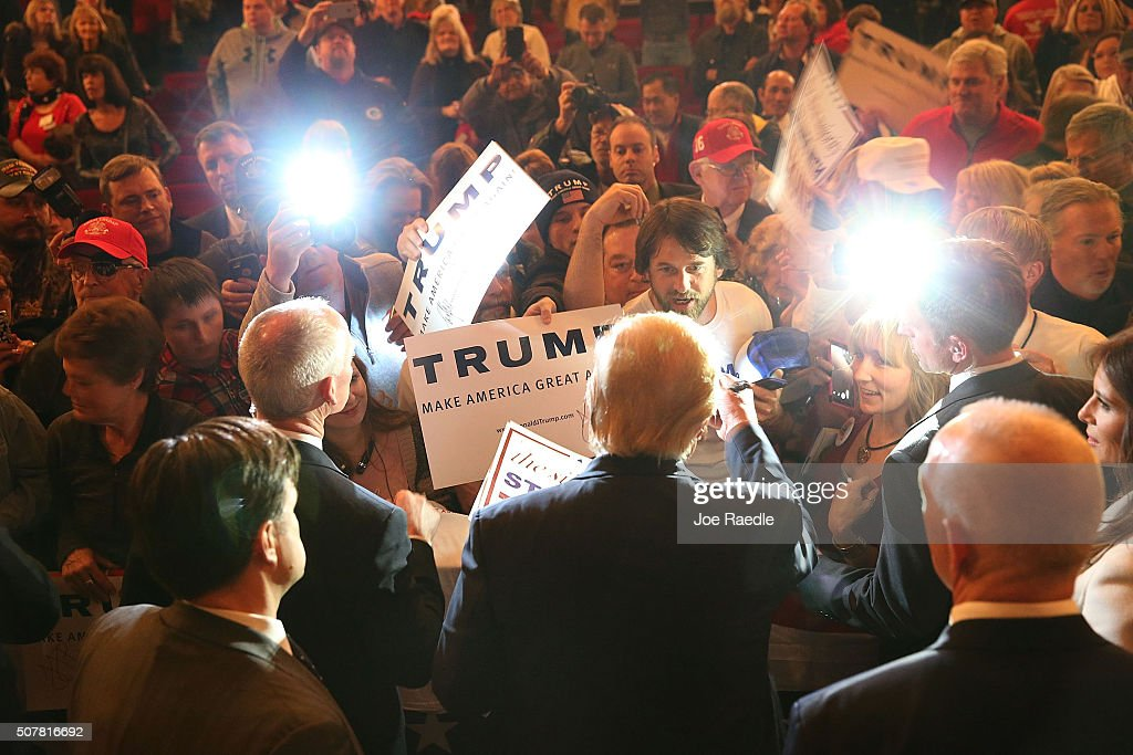 Republican presidential candidate Donald Trump greets people as he attends a campaign rally at the Sioux City Orpheum Theatre on January 31 2016 in...