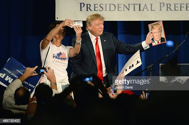 Republican presidential candidate Donald Trump holds a copy of TIME magazine with his likeness of the cover as a woman tries to take a selfie at the...