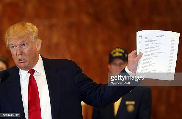 Republican presidential candidate Donald Trump holds a sheet of paper with his donations listed at a news conference at Trump Tower where he...