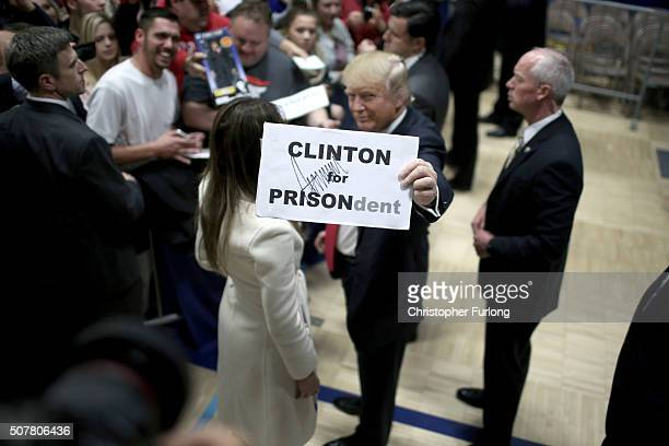 Republican presidential candidate Donald Trump holds a sign given to him by a supporter after a campaign rally at the Gerald W Kirn Middle School on...