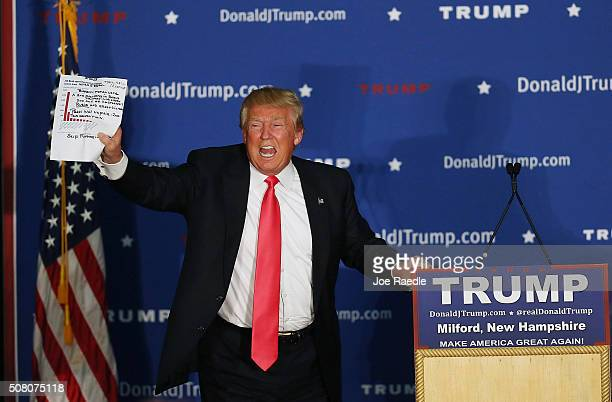 Republican Presidential candidate Donald Trump holds up a sheet of paper that blew off his podium during a campaign event at Hampshire Hills Athletic...